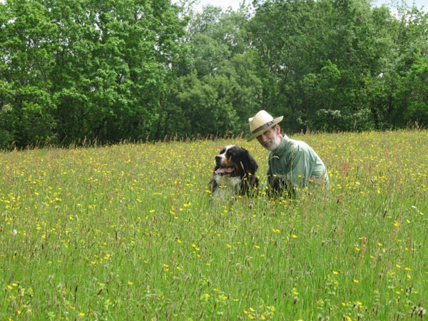 Andrew Hubbard sat in a field at South Yeo Farm West with his dog.