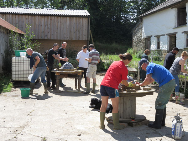 People working together to create a cob oven on a smallholder training day